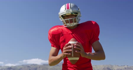 undefined : Front view of a mixed-raced American football player holding a ball at a sports field, in front of blue sky, in slow motion. Track and Field Sports Training in Stadium. Stock Footage