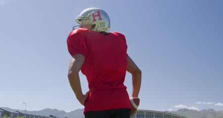 flexibilidade : Rear view of a mixed-raced American football player holding a ball at a sports field against a blue sky, in slow motion. Track and Field Sports Training in Stadium.