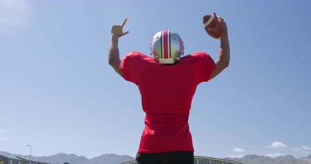 saltando : Rear view of a mixed-raced American football player holding a ball, raising his arms and pointing at a sports field, against a blue sky, in slow motion. Track and Field Sports Training in Stadium.