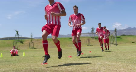 stepping : Front view of a team of Caucasian male football players wearing a team strip, training at a sports field in the sun, running and raising their legs high, in slow motion. Track and Field Sports Training in Stadium.