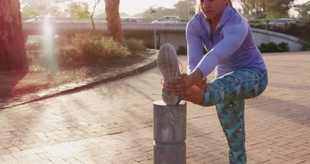 raffreddamento : Front view of a young Caucasian woman with long hair in a ponytail wearing sports clothes, stretching with one leg up on a post during a workout in an urban park, backlit by sunlight, slow motion