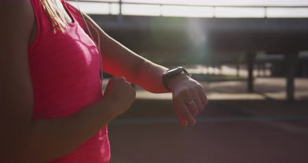 wearing earphones : Side view mid section of a young Caucasian woman wearing sports clothes looking at her watch during a workout in a park, slow motion
