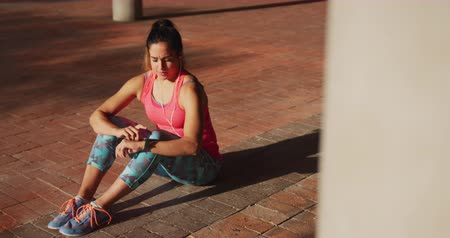 em desenvolvimento : High angle view of a young Caucasian woman wearing sports clothes sitting and looking at her watch during a workout under a bridge, slow motion