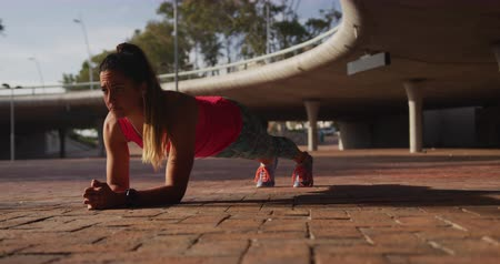 trecho : Front view of a young Caucasian woman wearing sports clothes doing plank during a workout under a bridge, slow motion
