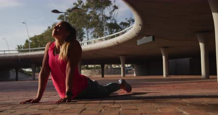 trecho : Front view close up of a young Caucasian woman wearing sports stretching up during a workout under a bridge, slow motion