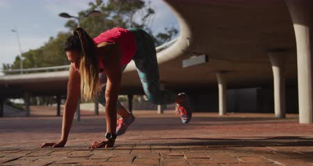 flexibilidade : Front view of a young Caucasian woman wearing sports clothes warming up during a workout under a bridge, slow motion Stock Footage
