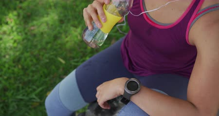 wearing earphones : High angle mid section view of a young Caucasian woman wearing sports clothes leaning sitting, drinking water and looking at watch during a workout in a park, slow motion