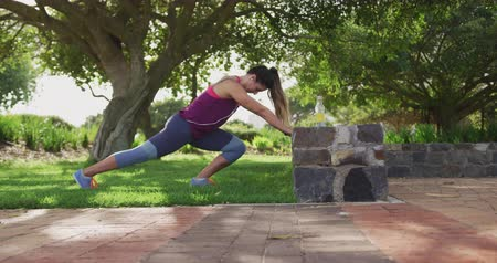 cooling : Side view of a young Caucasian woman wearing sports clothes stretching up by a low wall during a workout in a park, slow motion