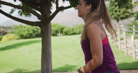 raffreddamento : Side view close up of a young Caucasian woman wearing sports clothes stretching up by a low wall during a workout in a park, slow motion