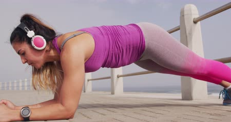 planking : Side view close up of a young Caucasian woman wearing sports clothes and headphones doing plank during a workout on a promenade, slow motion Stock Footage