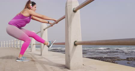 raffreddamento : Side view of a young Caucasian woman wearing sports clothes and headphones stretching up by the fence during a workout on a promenade, slow motion Filmati Stock