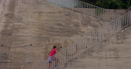 flexibilidade : Side view of a young Caucasian woman wearing sports clothes running up the stairs during a workout in park, slow motion Stock Footage