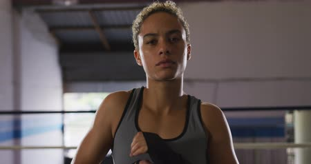 vest : Portrait close up of a mixed race female boxer with short curly hair wearing a grey vest at a boxing gym, looking straight to camera and flexing her muscles, slow motion