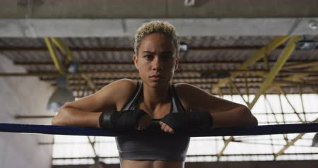 focussed : Portrait of a mixed race female boxer with short curly hair wearing a grey vest and with hands wrapped at a boxing gym, leaning on the ropes of a boxing ring, looking straight to camera, slow motion