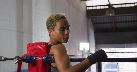 углы : Portrait of a mixed race female boxer with short curly hair wearing a grey vest and with hands wrapped, at a boxing gym, sitting in the corner of a boxing ring, turning around and looking to camera, slow motion