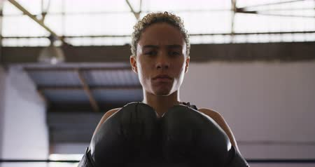 focussed : Portrait of a mixed race female boxer with short curly hair wearing boxing gloves, at a boxing gym, standing with gloves together, looking straight to camera, slow motion