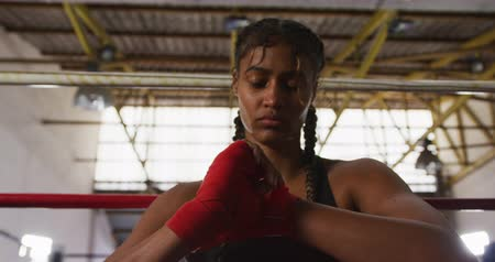 atlet : Front view of a mixed race female boxer with long, plaited hair, at a boxing gym, sitting in a boxing ring and wrapping her hands, slow motion Stok Video