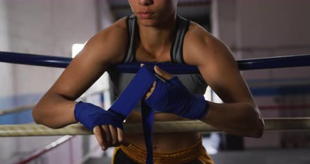 ラッピング : Front view mid section of a mixed race female boxer wearing a grey vest, at a boxing gym, standing in a boxing ring leaning against the ropes and wrapping her hands, slow motion