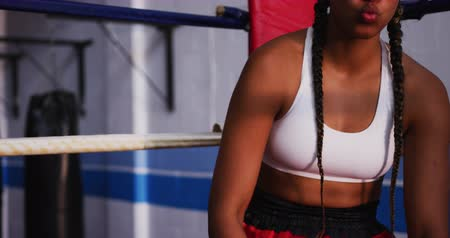 углы : Front view close up of a mixed race female boxer with long plaited hair at a boxing gym, sitting in the corner of a boxing ring wearing a gumshield, banging her gloves together, looking to camera and preparing to box, slow motion