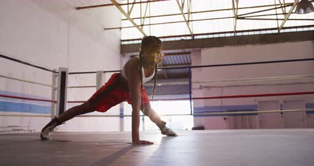atletický : Side view of a mixed race female boxer with long plaited hair wearing a vest and boxing shorts at a boxing gym, doing press ups with one arm in a boxing ring, slow motion
