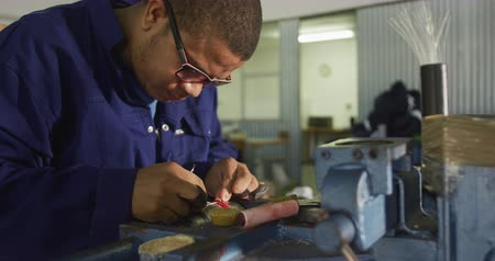 focussed : Side view of an African American man wearing glasses working in a workshop at a factory making cricket balls, sitting at a workbench holding thread and stitching a cricket ball, slow motion Stock Footage
