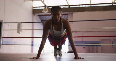 жилет : Front view of a mixed race female boxer with long plaited hair wearing a vest and boxing shorts at a boxing gym, doing press ups in a boxing ring, slow motion
