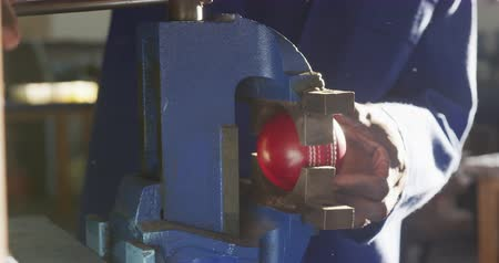 cricket : Front view mid section of an African American man working in a workshop at a factory making cricket balls, standing at a workbench tightening a vice on a cricket ball, slow motion Stock Footage