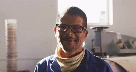 verimlilik : Portrait of an African American man wearing glasses working at a factory making cricket balls, standing and smiling to camera, in front of the machine that he operates, backlit, slow motion