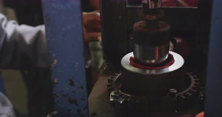 focussed : Side view close up of an African American man working at a factory making cricket balls, operating a machine that shapes the leather cover of the cricket ball Stock Footage