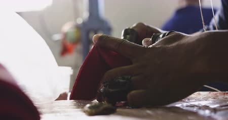 stiksel : Side view mid section of an African American man working at a factory making cricket balls, stitching parts of the leather cover of the cricket ball together, backlit