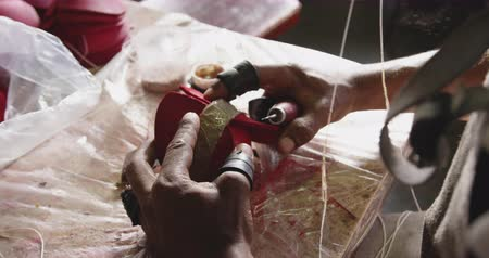 stiksel : Over the shoulder view of an African American man working at a factory making cricket balls, stitching parts of the leather cover of the cricket ball together