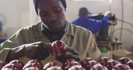 caixa de ferramentas : Front view close up of an African American man working in the workshop at a factory making cricket balls, sitting at a workbench with a crate of balls, holding one and finishing the seam with a hand tool