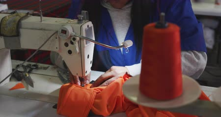 stiksel : Front view mid section of a woman using a sewing machine to stitch orange fabric at a sports clothing factory