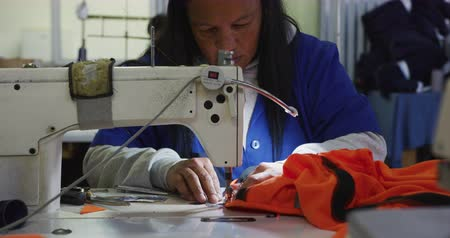 stiksel : Front view close up of a woman using a sewing machine to stitch orange fabric in a sports clothing factory Stockvideo