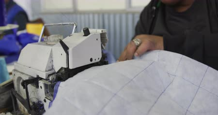 stiksel : Front view close up of an African American woman using a sewing machine to stitch quilted fabric at a sports clothing factory