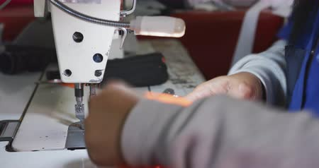stiksel : Side view mid section of the hands of a woman using a sewing machine to stitch orange fabric at a sports clothing factory