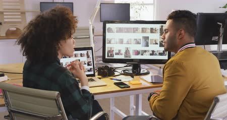 agência : Side view of a mixed race woman and man working in a creative office, using computers, discussing and shaking hands