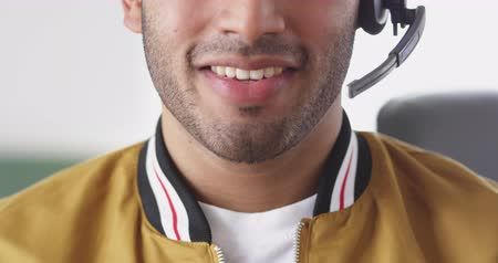 телефон доверия : Front view close up of a happy mixed race man working in a creative office, wearing headset, talking and smiling