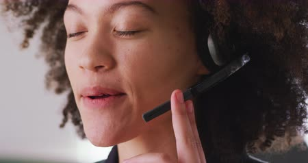телефон доверия : Portrait close up of a happy mixed race woman working in a creative office, wearing headset, talking and smiling, looking to camera Стоковые видеозаписи