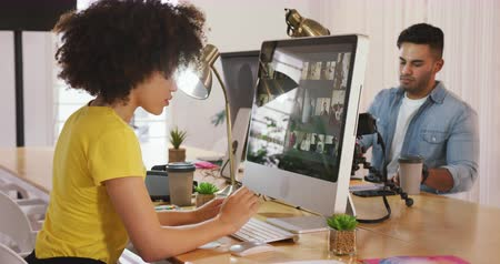 agência : Side view of a mixed race man and woman working in a creative office, looking at computer screen, woman typing Vídeos