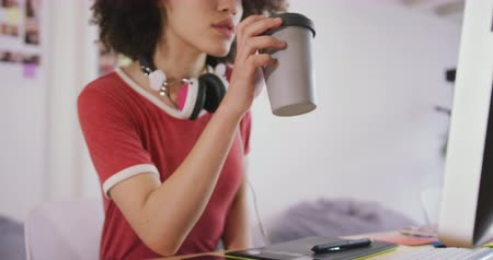 agência : Front view of a mixed race woman working in a creative office, drinking take away coffee and looking at computer screen, slow motion Vídeos