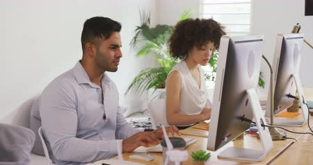 agência : Side view of a mixed race woman and man working in a creative office, sitting at desk looking at computer screens, discussing Vídeos