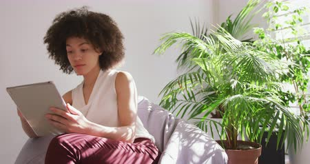 agência : Front view of a mixed race woman working in a creative office, sitting in an armchair, using a tablet computer, slow motion