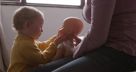 poppetjes : Front view of a Caucasian toddler enjoying family time at home, holding a doll and playing with it, the mother sitting on the bed, slow motion