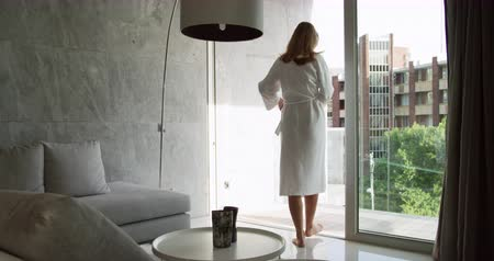 félrebeszél : Rear view of a Caucasian woman enjoying quality time in a hotel, standing in the living room looking put of the window, tying bathrobe, buildings outside, slow motion Stock mozgókép
