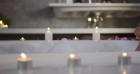 tımar : Side view close up of a Caucasian woman enjoying quality time in a hotel, lying in bathtub with candles, slow motion Stok Video