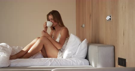 kahve molası : Side view of a Caucasian woman enjoying quality time in a hotel, sitting on bed in bedroom and drinking cofee, slow motion Stok Video