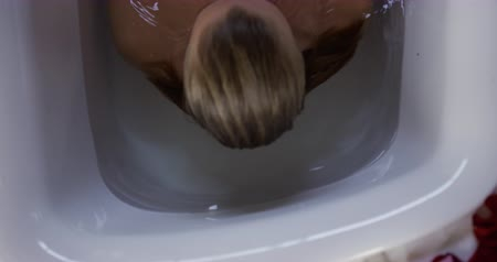 mosás : High angle front view of a Caucasian woman enjoying quality time in a hotel, lying down in bathtub with eyes closed, slow motion