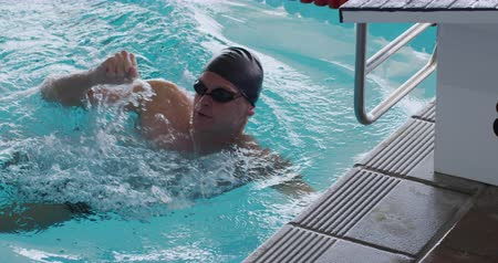 plavat : Side view of Caucasian male swimmer at swimming pool, swimming, holding starting block, raising his arm and shaking his fist in victory, in slow motion