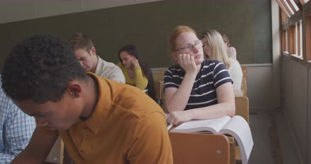nuda : Front view of a teenage Caucasian girl in a school classroom sitting a desk, leaning on her hand, thinking and looking out of the window, with teenage male and female classmates sitting at desks bust working around her, in slow motion
